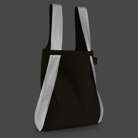 Bolsa-mochila plegable color negra con asas reflectantes como bolso